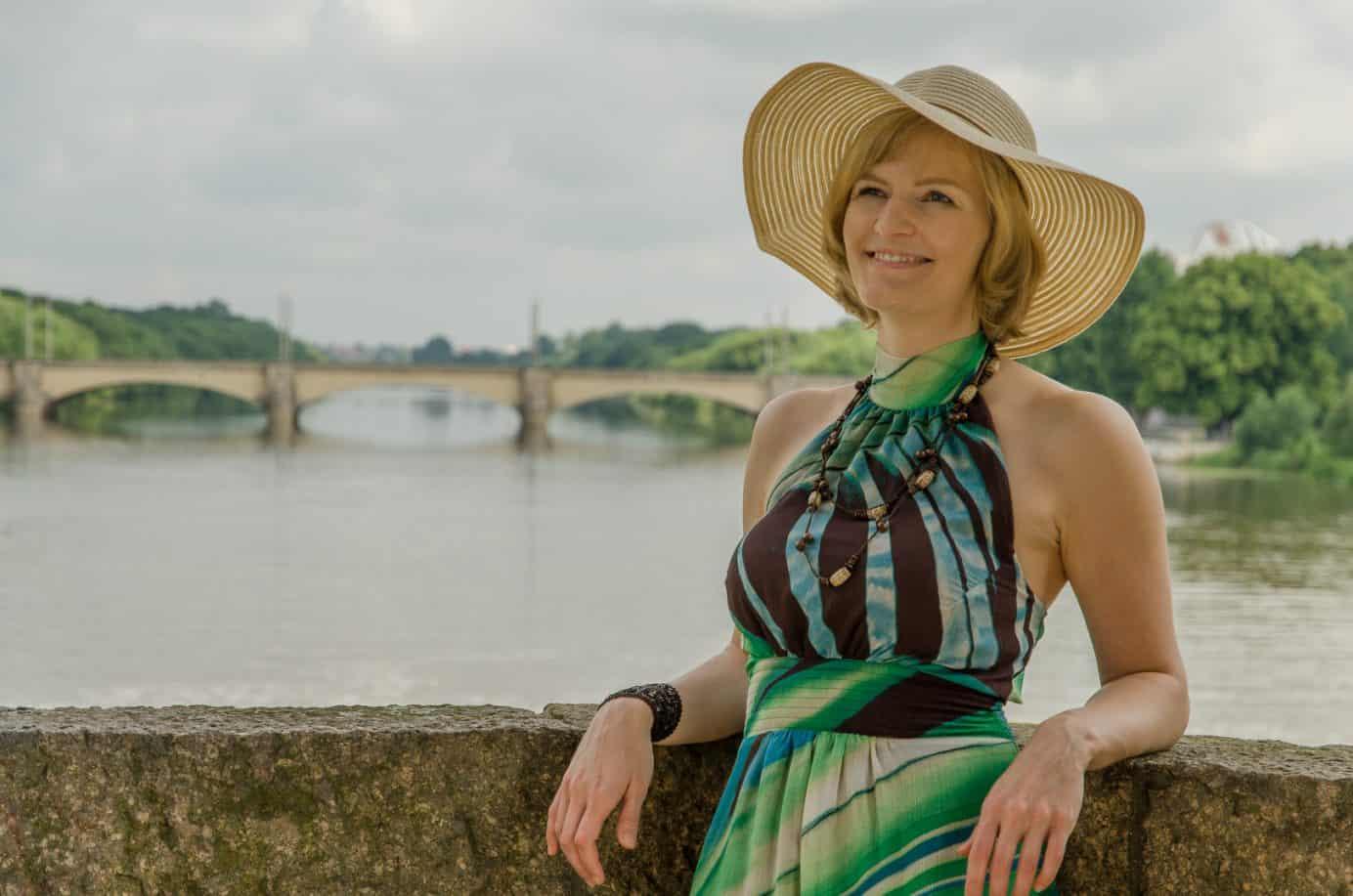 Lebensfrohe, junge Frau mit Hut und Sommerkleid auf einer Brücke mit Fluss, Brücke und Grün im Hintergrund